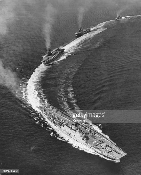 The Royal Navy Audaciousclass fleet aircraft carrier HMS Ark Royal maneuvers into line ahead of fleet carriers HMS Albion and HMS Ocean as they...