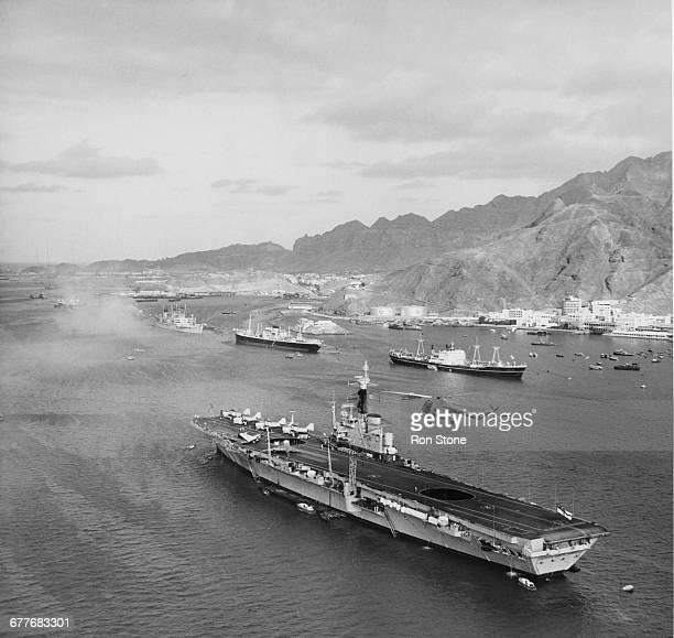 The Royal Navy Centaurclass light fleet aircraft carrier HMS Centaur with her straight axial flight deck at anchor in the Port of Aden whilst on...