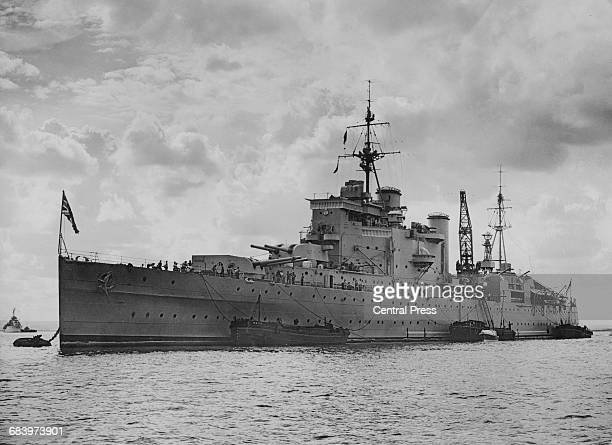 The Royal Navy Countyclass heavy cruiser HMS London at anchor deammunitioning and defuelling after returning from repairs after her rescue mission of...