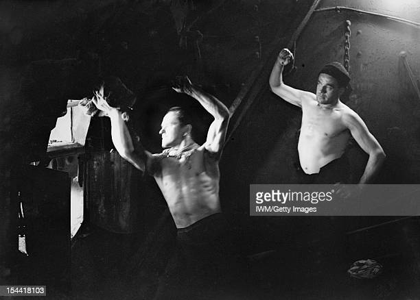 The Royal Navy During The Second World War A scene in the boiler room showing a bare chested stoker raking his fire while a similarly dressed...