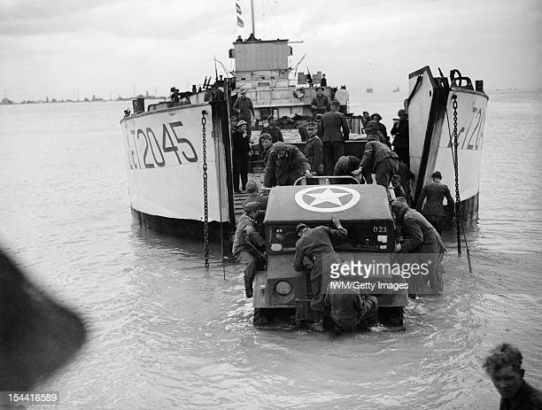The Royal Navy During The Second World War Operation Overlord June 1944 German prisoners of war helping to unload a jeep from LCT 2045 on the beach...