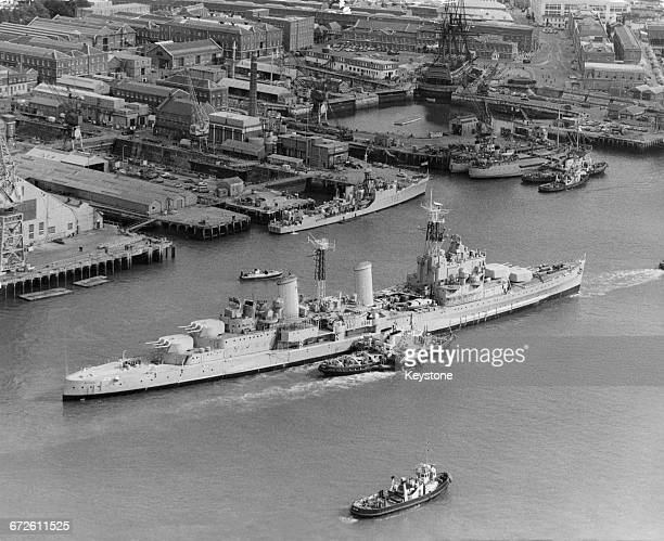 The Royal Navy Townclass light cruiser HMS Belfast under tow from tugboats passes the18th century 104gun firstrate ship of the line and Admiral Lord...