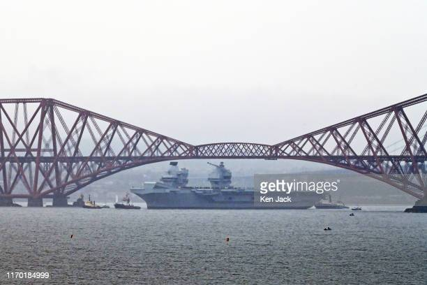 The Royal Navy's newest aircraft carrier HMS Prince of Wales sails under the iconic Forth Bridge in heavy rain to begin sea trials before joining the...