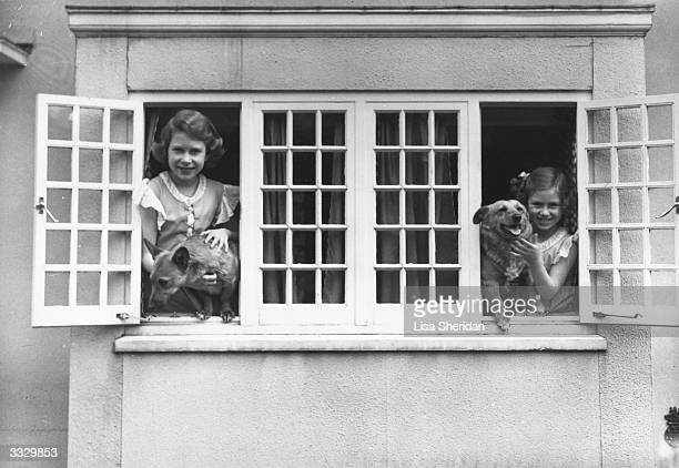The Royal Princesses Elizabeth and Margaret at the windows of the Royal Welsh House with two Corgi dogs June 1936