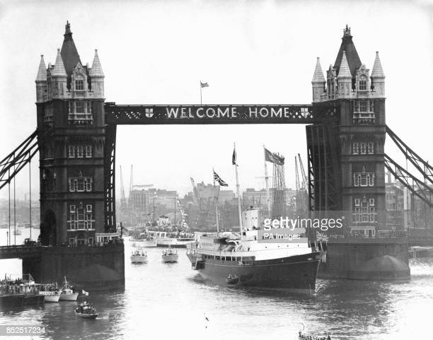 The Royal yacht Britannia passes through Tower Bride wearing a bold 'Welcome Home' as she enters the Pool of London ending a 30000 mile journey for...