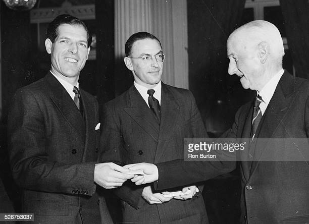 The Rt Hon Viscount Templewood presenting gold cigarette cases to Tony Mottram and Geoffrey Paish, at the Lawn Tennis Association's Annual Meeting,...