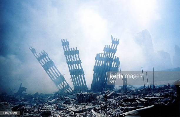 The rubble of the World Trade Center smoulders following a terrorist attack 11 September 2001 in New York. A hijacked plane crashed into and...