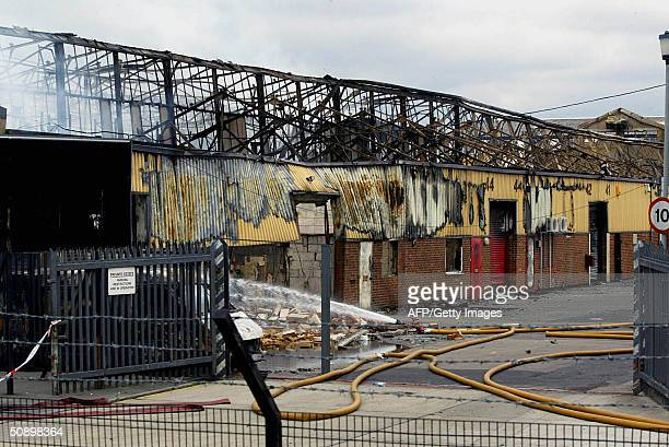 The ruins of a warehouse smolder after a twoday fire at a storage facility in London 26 May 2004 The fire in east London may have destroyed several...