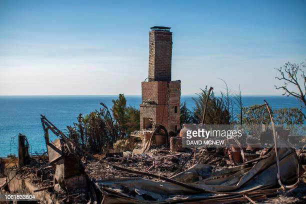 The ruins of an ocean view home are seen in the aftermath of the Woolsey Fire in Malibu California on November 14 2018 Firefighters backed by air...