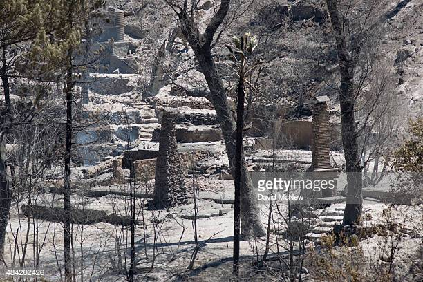 The ruins of burned houses are seen at the Cabin Fire in the Angeles National Forest on August 15 2015 north of Azusa California The fire has grown...