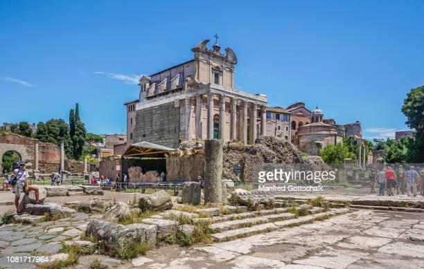 the ruins of the temple of caesar against the backdrop of the antonius and faustina temple which became the church of san lorenzo at the roman forum, rome, italy, june 28, 2018 - san stock pictures, royalty-free photos & images