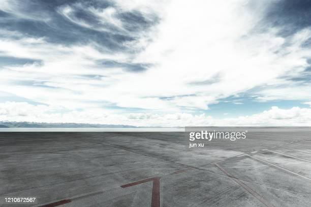 the runway under the blue sky and white clouds - airfield stock pictures, royalty-free photos & images