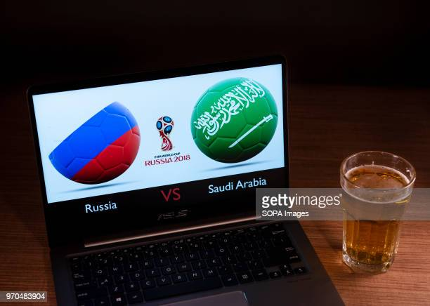 The Russia and Saudi Arabia flags seen together with the Russian 2018 World cup logo displayed on a laptop next to a glass of beer Opening Group A...