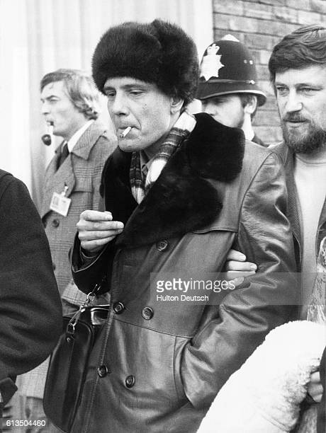 The Russian dissident Vladimir Bukovsky is escorted by a group of people including a policeman on his arrival at London Airport after being released...