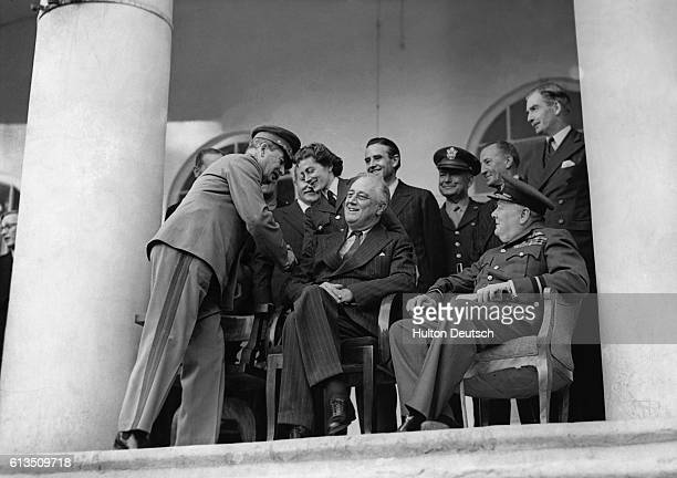 The Russian leader Joseph Stalin shakes hands with Miss Sarah Churchill whose father Sir Winston Churchill the British Prime Minister sits beside...