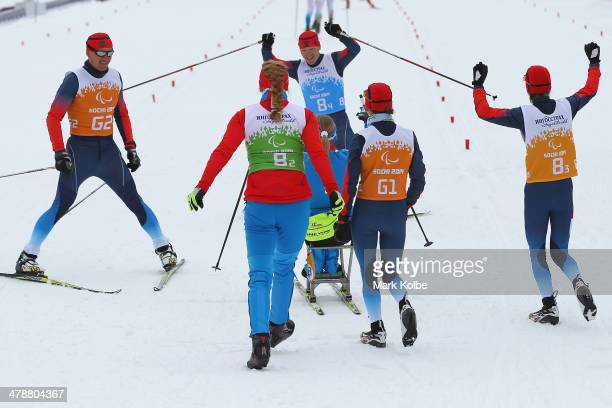 The Russian mixed relay team celebrate winning the gold medal as Nikolay Polukhin of Russia cross the finish line in the 4 x 25km Mixed Relay...
