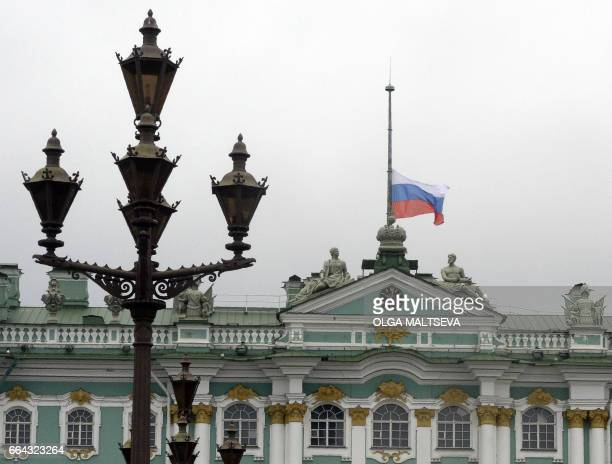 The Russian national flag flies at halfmast on top of the State Hermitage museum in central Saint Petersburg on April 4 2017 as a mark of respect for...