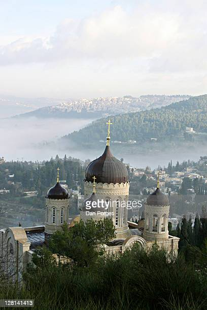 the russian orthodox gorny convent high on slopes above ein kerem where john the baptist was born and where mary visited johnãs mother elizabeth. village of ein kerem seen below, jerusalem neighborhoods on the hills and fog in the valley. israel - liz vega fotografías e imágenes de stock
