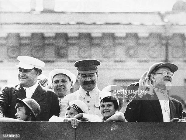 The Russian politicians Josef Stalin and Mikhail Kalinin watch a worker's parade in Red Square with the Bulgarian politician George Dimitrov and...
