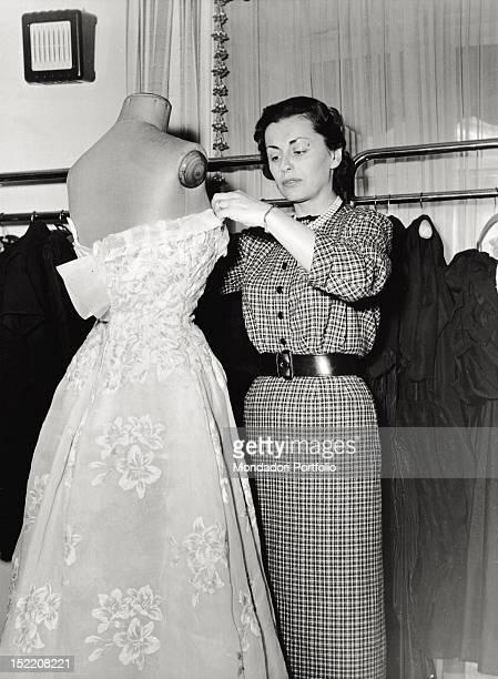 The Russian Princess and fashion designer Irene Galitzine arranging a dress Rome 1950s