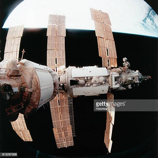 The Russian Space Station Mir in orbit above earth as seen from the aft flight deck of the Space Shuttle Atlantis while it was linkedup with the...