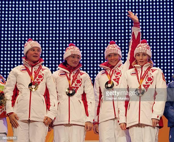 The Russian team of Anna Bogaliy Svetlana Ishmouratova Olga Zaitseva and Albina Akhatova receive the Gold Medal in the Womens Biathlon 4x6km Relay at...