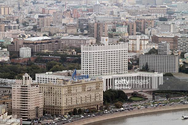 The Russian White House a government building right stands behind a building displaying an OAO Gazprom sign in Moscow Russia on Tuesday Sept 13 2011...