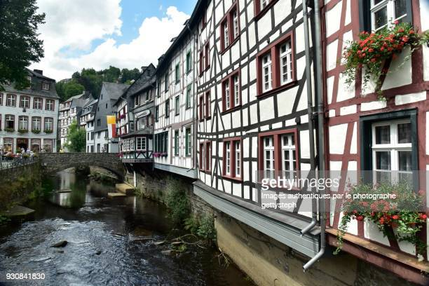 The rustic half-timbered structure overhanging Roer River
