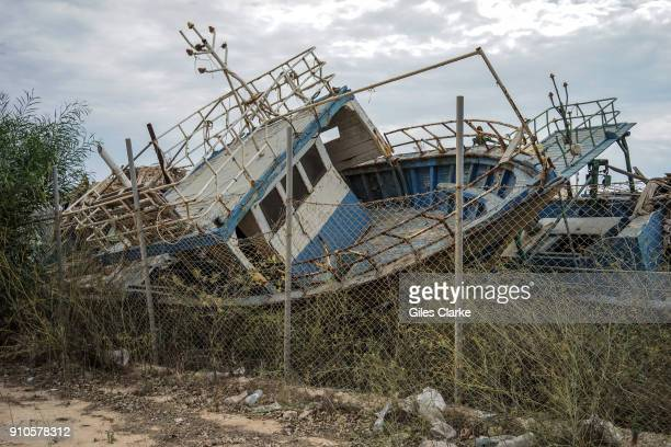 The rusting remains of fishing boats used to ferry migrants from the coast of North Africa now lie in maritime graveyard in Lampedusa Italy Photo by...