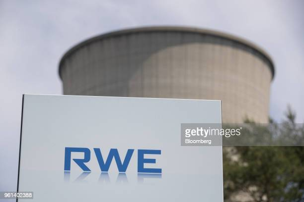 The RWE AG logo sits on a sign as a cooling tower stands at the company's gas powered power plant in Lingen Germany on Tuesday May 22 2018 RWE is...