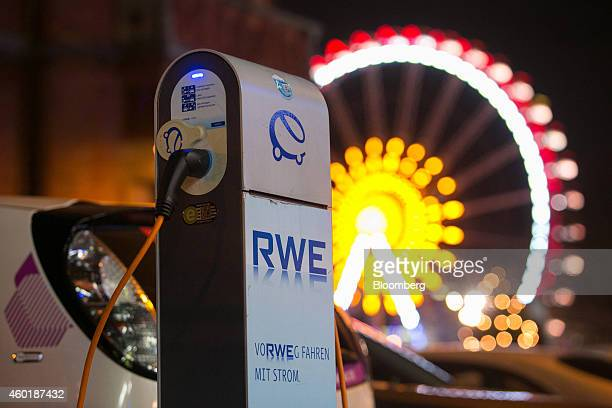 The RWE AG logo sits on the side of an electric automobile charging station as a ferris wheel stands illuminated beyond in Berlin Germany on Monday...
