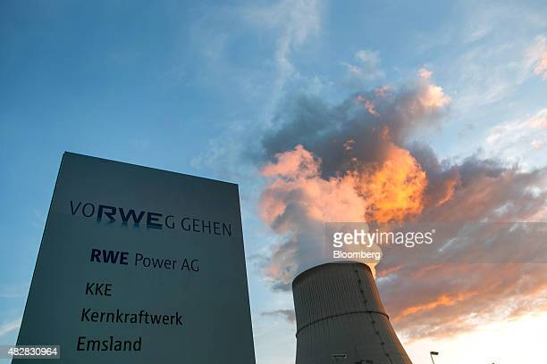 The RWE logo sits on a sign as a cooling tower emits vapor into the sky at Emsland Nuclear Power plant operated by RWE AG in Emsland Germany on...