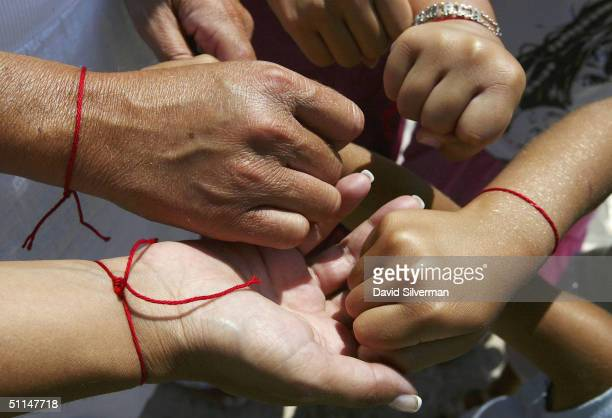 The Saadoun family from Paris France wear their Kabbalah Red String Bracelets while praying at the Western Wall Judaism's holiest site August 6 in...