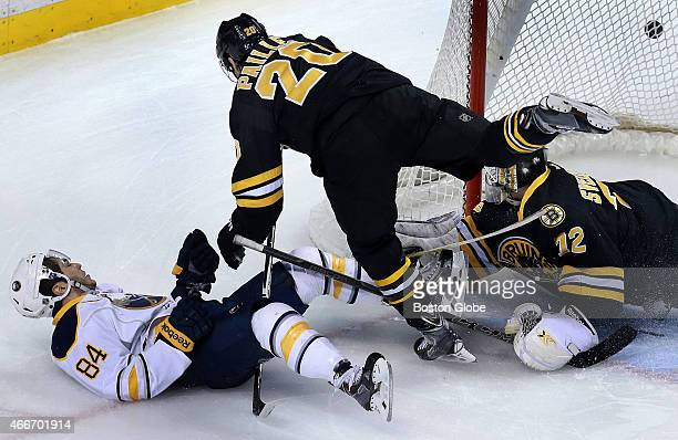 The Sabres' Philip Varone is knocked down by a flying Bruins winger Daniel Paille as the puck ends up behind the net of Boston goalie Niklas Svedberg...