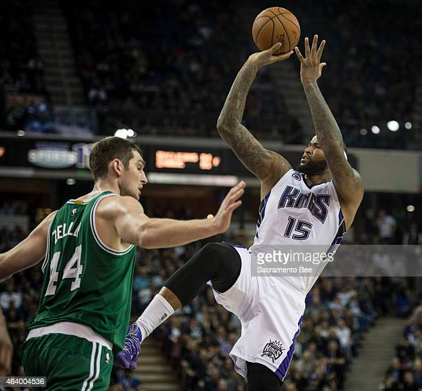 The Sacramento Kings' DeMarcus Cousins hits an off balance shot as he's fouled by the Boston Celtics' Tyler Zeller in the third quarter on Friday Feb...