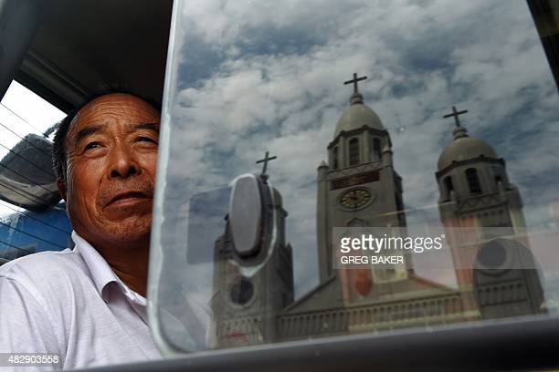 The Sacred Heart of Jesus Catholic church is reflected in a window as a man looks out from a van after Father Joseph Zhang Yilin was ordained as a...