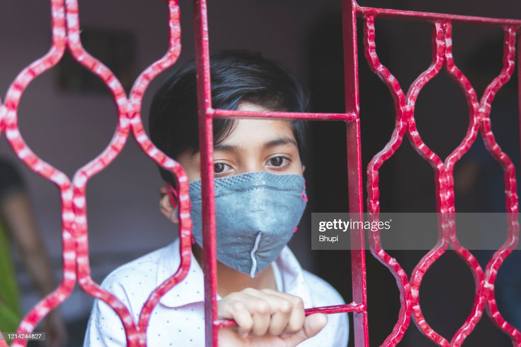The sad boy is protecting herself and wearing a mask against the corona virus : Stock Photo
