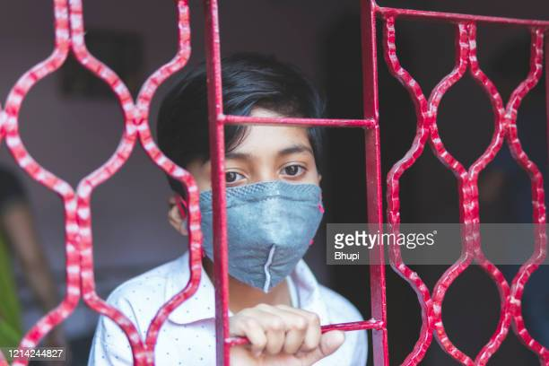 the sad boy is protecting herself and wearing a mask against the corona virus - lockdown stock pictures, royalty-free photos & images
