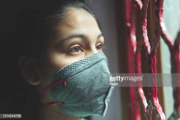 the sad girl is protecting herself and wearing a mask against the corona virus - curfew stock pictures, royalty-free photos & images