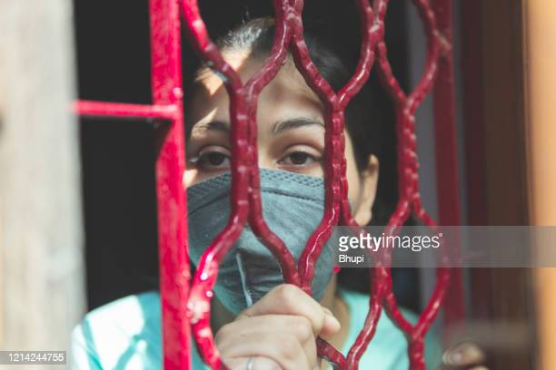 the sad girl is protecting herself and wearing a mask against the corona virus - lockdown stock pictures, royalty-free photos & images