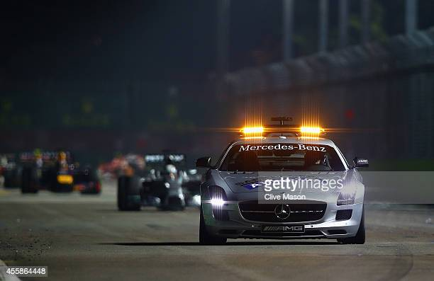 The Safety Car drives ahead of Lewis Hamilton of Great Britain and Mercedes GP and Sebastian Vettel of Germany and Infiniti Red Bull Racing during...