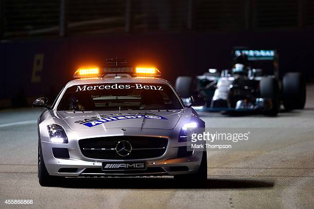 The Safety Car drives ahead of Lewis Hamilton of Great Britain and Mercedes GP during the Singapore Formula One Grand Prix at Marina Bay Street...