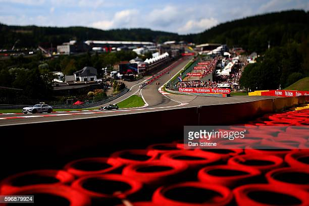 The safety car drives ahead of Nico Rosberg of Germany and Mercedes GP Daniel Ricciardo of Australia drives the Red Bull Racing Red BullTAG Heuer...