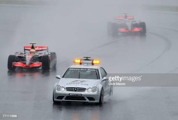 The safety car guides the leading car of Lewis Hamilton of Great Britain and McLaren Mercedes second placed car of Fernando Alonso of Spain and...