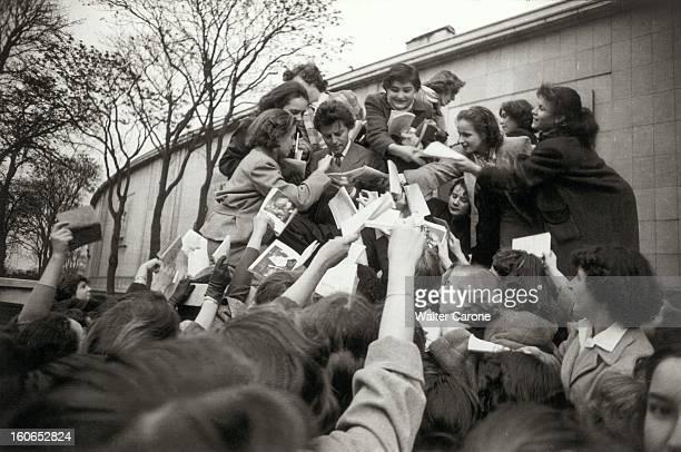The Saga Of The National Populaire Theater Gérard PHILIPE signant des autographes à une meute de jeunes filles venant d'assister à Chaillot aux...