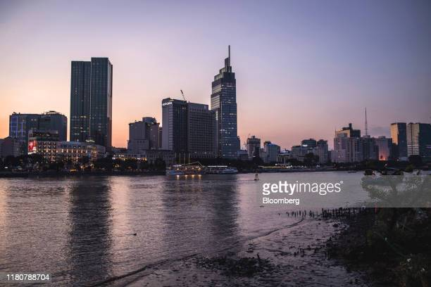 The Saigon Times Square building left the Vietcombank Tower center and other commercial buildings stand along Saigon River at dusk in Ho Chi Minh...