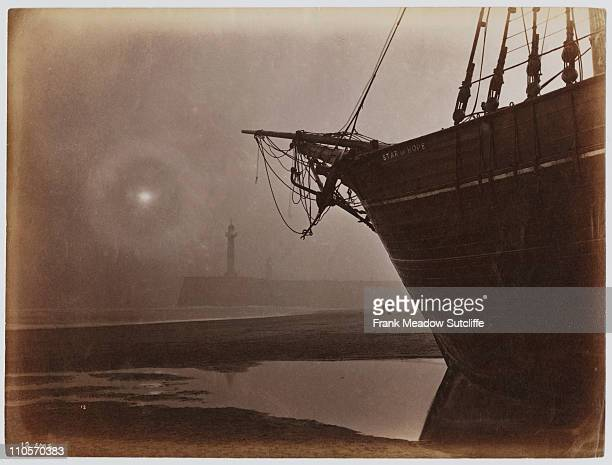 The sailing ship 'Star of Hope' at low tide near the lighthouse in Whitby harbour North Yorkshire circa 1890