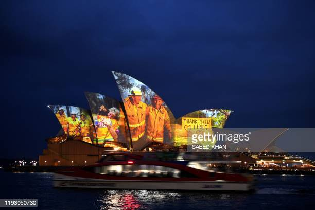 TOPSHOT The sails of the Opera House are lit with a series of images to show support for the communities affected by the bushfires and to express the...
