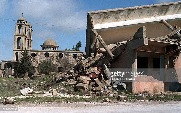 The Saint George Greek Orthodox church appears 02 August 1999 behind the ruins of a building destroyed in the village of Kuneitra on the Golan...