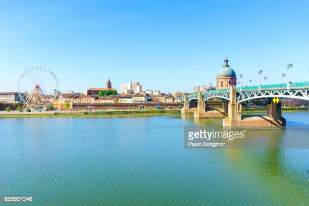 The Saint-Pierre bridge and Ferris Wheel and Hospital De La Grave in Toulouse, France